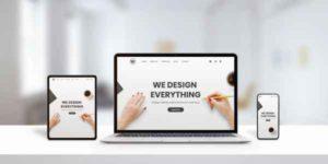 Agentur Webseiten auf unterschiedlichen modernen Endgeräten - Laptop, Notebook, Tablet, Smartphone. Display-Konzept in moderner flache Seitengestaltung auf einem Schreibtisch im Büro