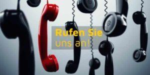 Mehrere Telefonhörer hängen an ihren Kabeln - einer ist rot